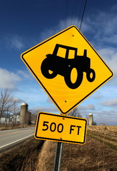 Caution and keep a 500 foot distance between yourself and the farm vehicle ahead of you.